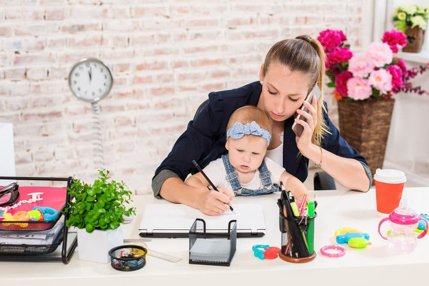 FMLA Family Business - telecommute Businesswoman and mother with kid is making a phone call. At the workplace, together with a small child